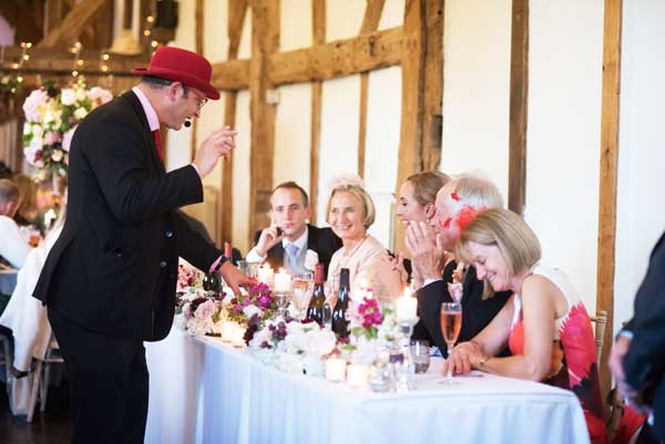 laughing guests at a wedding watching the magician