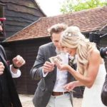 Bride and groom looking at a £20 note with their face on it. Magic trick at their wedding