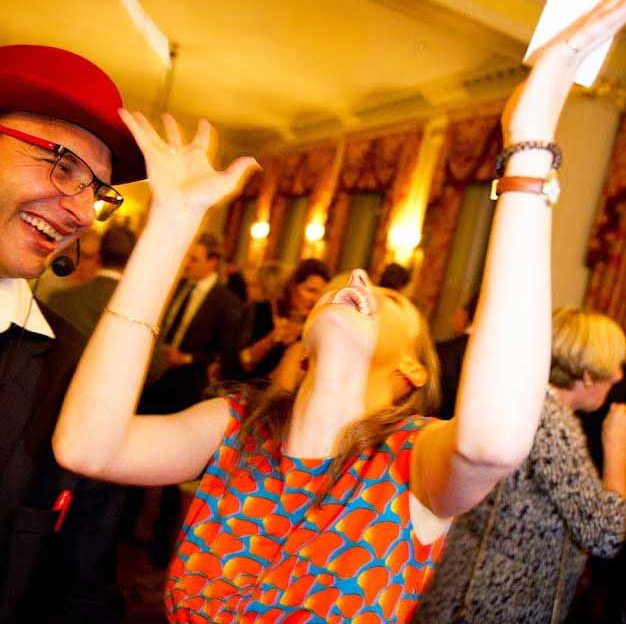A woman throws her hands up and her head back in astonishment at the party magician