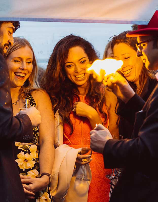 The Magician creates a ball of fire at a partysurrounded by people laughing