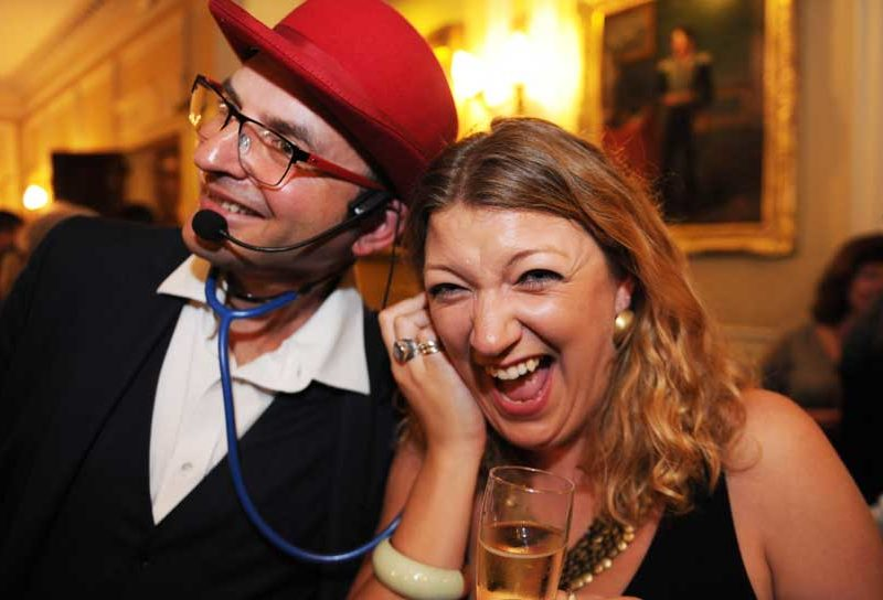 A lady holding a stethoscope to her ear and laughing with the magician at a birthday party