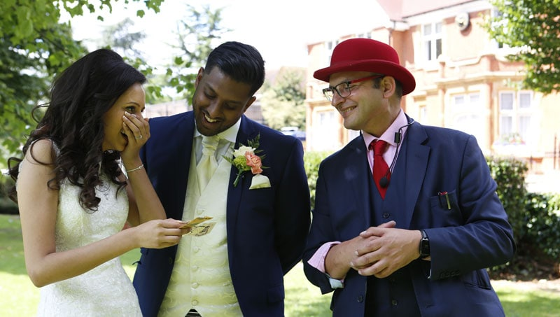 Indian groom laughing and Asian bride with her hand over her mouth laughing and gasping at the incredible magic trick