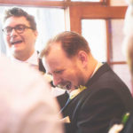 Groomlaughing in astonishment at a magic trick during a gay wedding