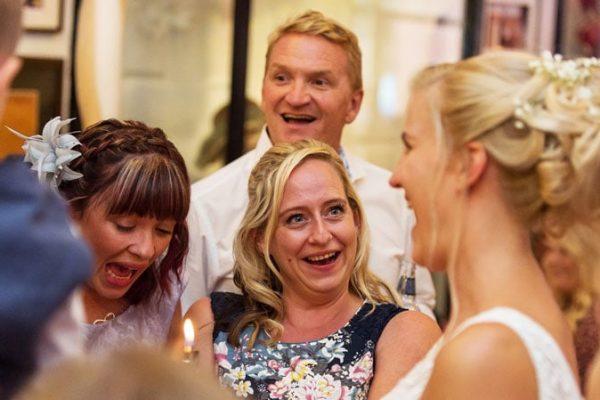 Bride enjoying magic with astonished shrieking bridesmaid