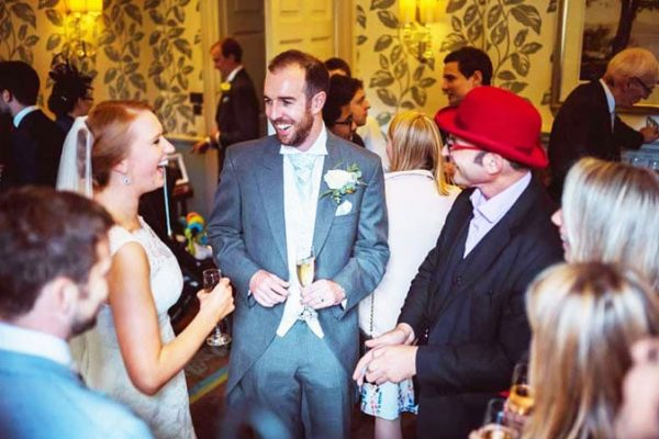 Bride and Groom laughing with the magician at a Surrey wedding